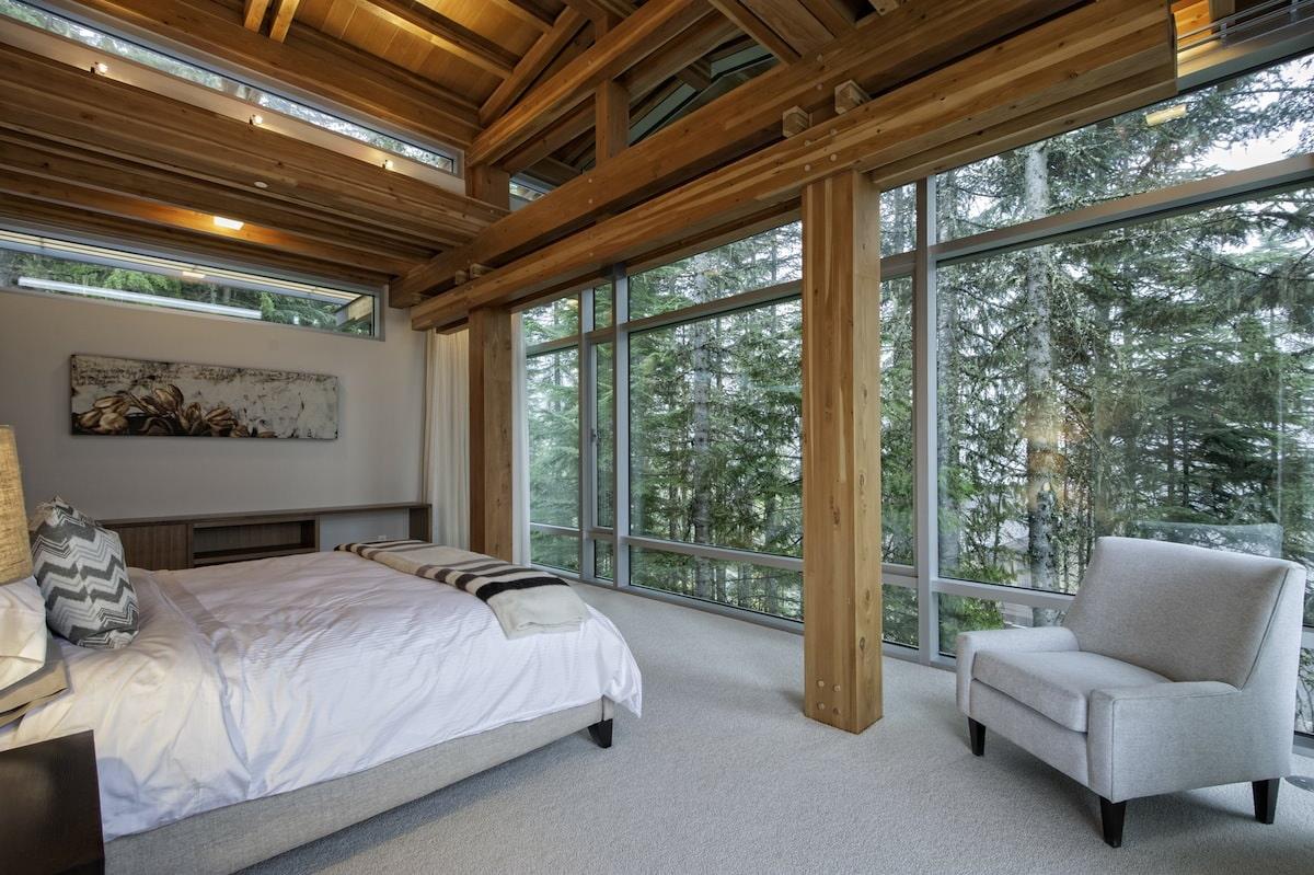 Интерьер спальни в загородном доме с панорамными окнами